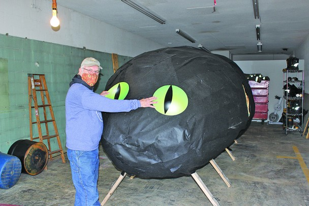 Burning Beetle volunteer Hank Fridell positions the huge eyes on the 2021 beetle which is under construction at the fire hall in Custer. After the facial features are attached, the huge wood and fabric monster will be moved to Pageant Hill on Saturday. There it will be mounted on a pyre and filled with fireworks to be set ablaze in this year's Burning Beetle event. Torch time will be about 5:15 p.m. following the torch march from the school parking lot which starts at 5 p.m.