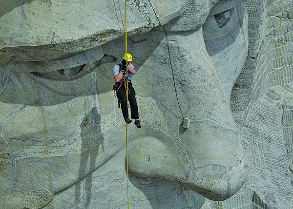 — A member of the Mount Rushmore National Memorial Rope Access Team hangs near the nose of Abraham Lincoln while assessing cracks on the former president's face. The team accesses the memorial's faces from the top and specializes in working directly on the surface of the sculpture. [Submitted Photo/NATIONAL PARK SERVICE - BLAINE KORTEMEYER]