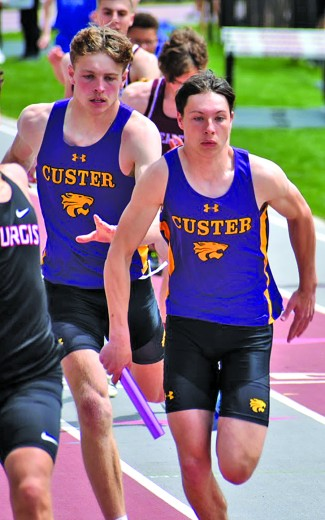 Jace Kelley takes off for his leg of the 400 relay after receiving the baton from Gage Tennyson at last week's Black Hills Conference Meet. Kelley, Tennyson, Daniel Sedlacek and Blake Boyster combined to win the event at the meet, breaking the meet and school record in the process. The four broke their own school record they had set the week before
